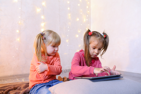 Cute little girls play in computer games on device or watch cartoons