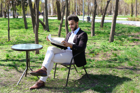 Nice man sits on chair near table, hold newspapers in hands. Guy has beard, short hair and dimples on cheeks. Man dressed in black jacket, white jeans and blue shirt, brown shoes. Concept of places for reading quite clean parks.