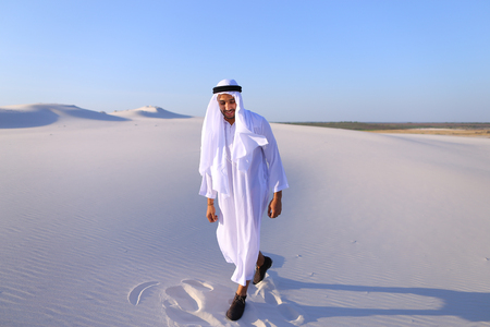 Handsome Arab man dances on spot and drives feet along soft white sand in middle of bottomless desert.