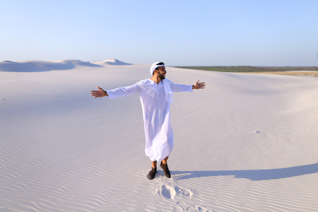 Stately young sheikh walks on foot along bottomless desert leaving traces on sand, enjoying warmth of day. Stock Photo