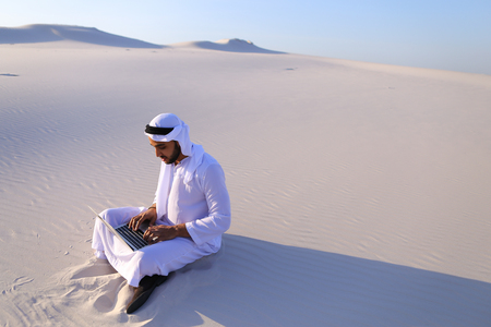 Successful young businessman male Muslim uses laptop to build drawing in Photoshop and prints fingers on laptop sitting on white sand in bottomless wide desert in afternoon against blue sky.