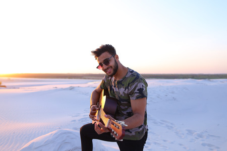 Close-up portrait of young Arab man who, with smile on face, plays favorite melody on musical stringed instrument, in middle of wide sandy desert on warm summer evening at sunset. Banco de Imagens