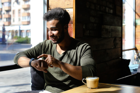 Mullato guy sits in caf near wooden table and looking in window. Man just ordered coffee. Handsome boy has dark hair, beard and dimples on cheeks, wears watch on hand. Concept of well-paid job business for young people places for relax.