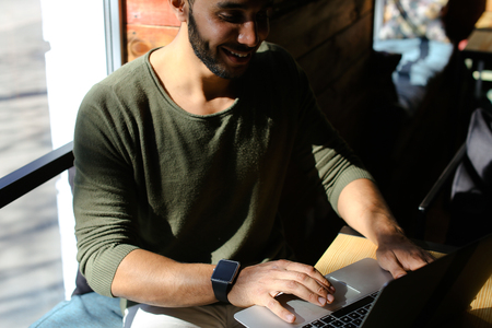 Insurance agent checks mail and clicking on keyboard. Boy dressed in khaki pullover. Attractive man has dimples, beard, full lips and black hair, long fingers. Concept of modern technologies and work in Internet online wifi.
