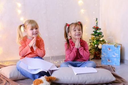 Concept van een gelukkige en zorgeloze jeugd, heldere en onvergetelijke New Years childrens emoties, kerstcadeaus en de kerstman, geheime verlangens aan de vooravond van vakantie, decor en helder feestelijk interieur. Stockfoto