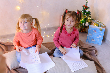Concept of happy and carefree childhood, bright and unforgettable New Years childrens emotions, Christmas gifts and Santa Claus, secret desires on eve of holidays, decor and bright festive interior.