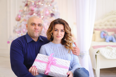Concept of loving husband and wife, gifts for loved ones, family values and warmth of relationships, care and attention, pleasant surprises on New Years Eve and Christmas mood. Stock Photo