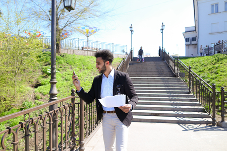 Man talking by phone, holds papers in hands and agreed with interlocutor. Guy has short dark hair, beard and dressed in black jacked, white jeans. Concept of modern technologies and work in holding. Stock Photo