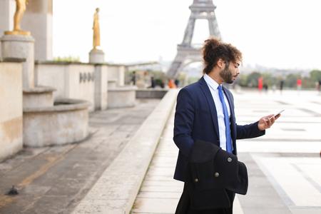 ハンサムの半分のナイジェリアとフランス語は、バック グラウンドでエッフェル塔と電話で呼び出し元恋人を男します。黒のスーツに青いネクタイ 写真素材