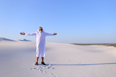 Concept of Arab and Muslim men, united Arab emirates and beautiful landscapes, sheikh in desert and seclusion from nature, Emiratis national clothes, good mood and enjoyment of life. Stock Photo