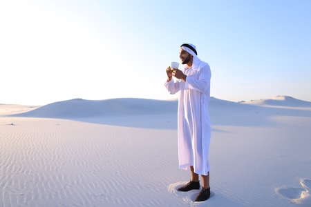 Concept of Arab and Muslim men, united Arab emirates and beautiful landscapes, advertisement of travel company, national clothes of emirates, good mood and happy emotions. Stock Photo