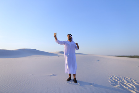 Concept of Arab and Muslim men, modern technology and gadgets, united Arab emirates and beautiful landscapes, sheikh in desert and seclusion with nature, national clothes and traditions. Stock Photo