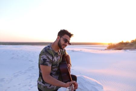 Concept of handsome Arab young man, hobby or favorite thing to do, learning or playing stringed musical instruments, good mood and positive emotions, beautiful scenery and amazing travel.