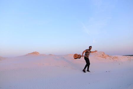 Young Muslim male performer and singer walks through sandy desert with guitar in hands,
