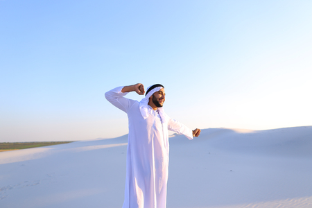 Concept of Arab and Muslim man, united Arab emirates and beautiful landscapes, sheikh in desert and solitude with nature, Emirati national clothes, good mood and happy emotions.
