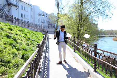 Attractive person talks by phone and walking on bridge. Man joyfully puts hands up with papers. Guy has short dark hair, beard, sunglasses on pocket and dressed in black jacked, white jeans. Concept of modern technologies fast work of Internet free calls always in touch.