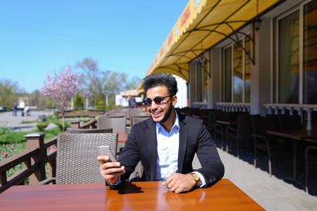 Man sits by table, put hand on chair stool and answered on phone call. Attractive guy has short dark hair, beard and wears watch on hand. Handsome person dressed in suit. Concept of new technologies apps for work free calls and advantageous tariff plan. Stock Photo