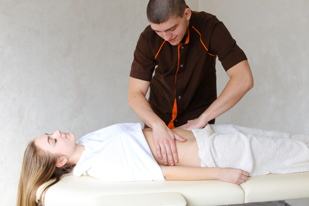 Friendly and professional guy doctor and masseur conducts strengthening and healing procedure for abdomen and body as whole, communicates and tells useful medical information that came to girl who lies on couch up to half covered with terry towel in light cosmetology salon.