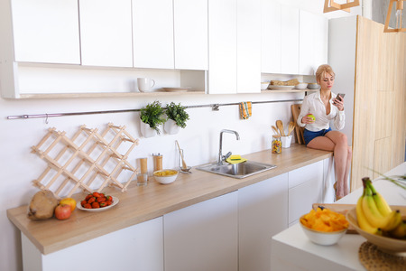 Cute woman using modern device, mobile phone reads useful articles about nutrition or orders dinner home, throws up and bites piece of green apple, smiles and laughs, sitting on surface of kitchen table among cutting boards and cabinets. Blond woman of European appearance dressed in white blouse with long sleeves and blue denim shorts. Concept beautiful and happy people, gadgets and technology, cooking healthy food, healthy vegetables, fresh vegetables and fruits, design and modern interiors, technology and equipment for home kitchens, vegetarianism and veganism.