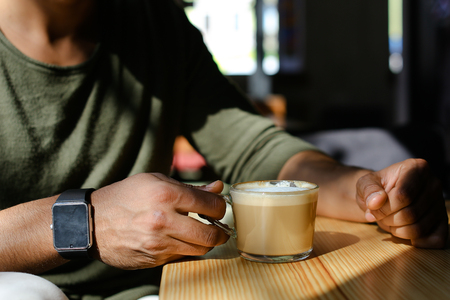 Close-up shooting, man sitting in cafe and drinking hot coffee with milk. Boy dressed in khaki pullover. Attractive mullato has dimples, beard, full lips and black hair. Concept of modern places for young people cheap prices.