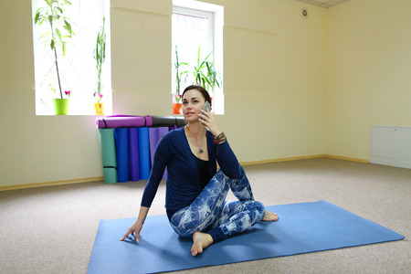 Beautiful girl check correctness of sun salutation on laptop. Lady strengthens all body major muscle groups in surya namaskar. Concept of online tutorial, using advanced technologies. Banco de Imagens