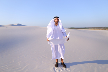 Beautiful Emirate Sheikh businessman studying project of future construction of complex, standing in middle of bottomless desert with white clean sand on clear warm day against blue sky.