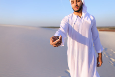 Close-up of face and hands of young Muslim man who takes sand into hand and blows small white grains of sand through fingers