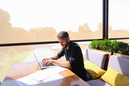 Tired quantity surveyor working at cafe table with diagram and statistic documents. Persistent man dressed in classic black shirt sitting at sofa near green indoor plants. Concept of  preparing estimates and costs of work, keeping track variations to contract affect costs and creating reports to show profitability. Stok Fotoğraf