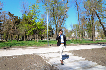 Smiling man dancing in park after exam and holds jacket in hands. Boy has beard, short hair and dimples on cheeks. Boy dressed in brown belt on white jeans and blue shirt, wears sunglasses. Concept of work after graduation and young specialists.