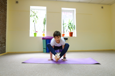 Beautiful smiling young woman of European appearance sits on mat for fitness and performs asanas from yoga, female hangs in air and holds only on hands. Girl dressed in comfortable sports black tights and white T-shirt. Room spacious and light, under wall compiled yoga mats. Concept of importance of healthy lifestyle and health care.
