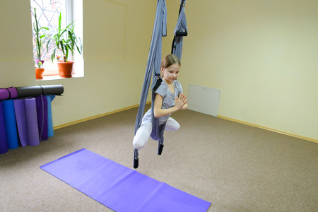 Beautiful girl of American appearance performs acrobatic elements in air, child concentrates and calmly holds on acrobatic ropes. Room nice warm lighting, walls delicate yellow and large windows, on windowsill pots with flowers, under wall  folded rugs for fitness. Concept of importance of physical exercises for children, desire to develop, need for favorite lesson.