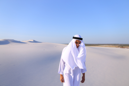 Cheerful Muslim guy walks along white sand of wide desert on warm summer evening. Stock Photo