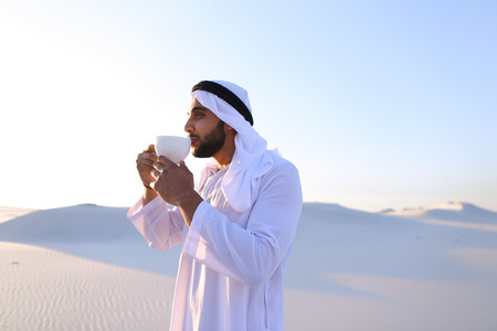 Portrait confident and happy male Muslim who drinks invigorating coffee drink from white cup and enjoys calm morning Stock Photo