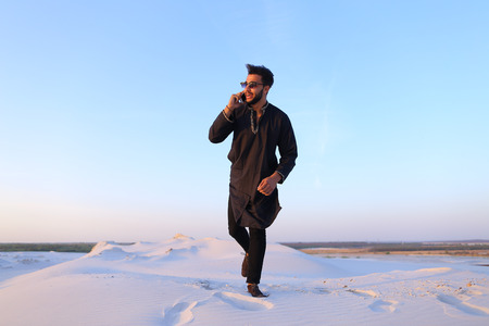 Modern Muslim chats on smartphone with smile on face and bounces on spot, spreading arms and legs to sides, being in bottomless desert with white and clean sand on clear spring evening.