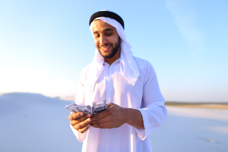 Handsome young Emirate in reckless mood recounts and examines banknotes, can not believe in own happiness or mirage, smiles and laughs throwing money down wind, standing in middle of bottomless desert with white sand on sunny summer day.
