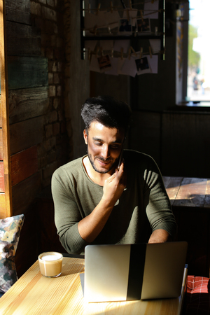 Mulatto sitting by table near laptop. Attractive man with dimples looks out of window and drinks coffee. Muslim ends conversation on phone, starts work with laptop. Concept of modern technologies wifi free Internet.