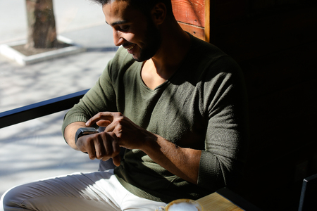Arab guy sits in caf and texting e-mail by smart watch. Happy boy has dimples, beard, full lips and black hair. Person dressed in khaki pullover. Concept of modern technologies and good atmosphere.