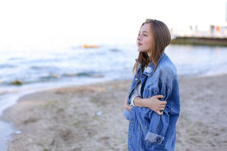 Beautiful young woman with necessary smile looks afar at sea waves, closes eyes with pleasure and listens to sound of surf, poses and warms from cool wind from sea on clear cool evening. Woman of European appearance with blond mid-length hair dressed in black pants, white T-shirt with bright pictures on top of which blue denim jacket stands against blue sea and sky. Concept beautiful and happy people, unity with nature, joyful and cheerful mood, fashion and style, natural and natural beauty, rest by sea and enjoyment of sea breeze, summer heat in resort city, advertising of womens clothing or cosmetics.