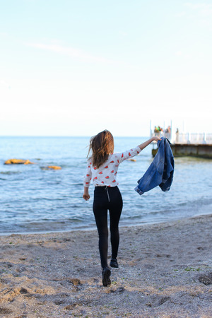 Smiling female walks along beach and enjoys nature, with broad smile on face jumping in place and raising hands upwards, squinting against bright sunlight, shielding eyes with hands. European-looking girl with medium-length blond hair dressed in black pants, white T-shirt with bright pictures on top of which blue denim jacket. Concept beautiful and happy people, unity with nature, joyful and cheerful mood, fashion and style, rest by sea and enjoyment of sea breeze, summer heat in resort city, advertising of womens clothing or cosmetics.