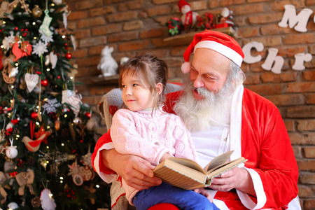 Inquisitive female child listens attentively to interesting story from book read by Santa Claus in cozy and spacious room decorated for New Years holidays with large floor lamp, walls on which Christmas posters hang, high bright tree under gifts lie boxes tied Ribbons. beautiful European-looking girl dressed blue jeans pink warm sweater. gray long beard red suit white trim pointed cap pompon end. Concept of traditions family happy Year, cherished desire, laughter carefree childhood children, interior decorations, desired positive emotions eve holidays, active pastime children foolishness, holiday attributes symbols , fairy tales magic.