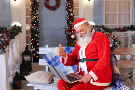 Cheerful Santa Claus making video call in cozy apartments. Gladden man in red costume satisfying with joyful ambience. 스톡 콘텐츠