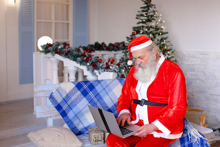 Cheerful Santa Claus making video call in cozy apartments. Gladden man in red costume satisfying with joyful ambience. Stock Photo