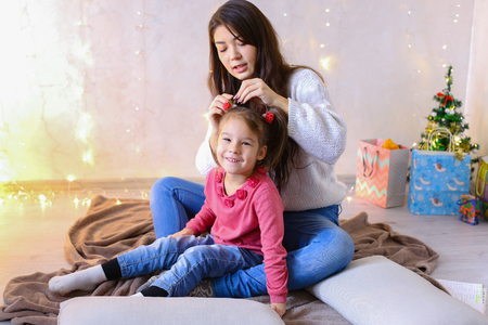 Beautiful girl and elder sister of small female child cares for younger sister and talks, hugs and braids up hair on head, fools around and laughs cute in family way, sitting on floor in bright room against backdrop of glowing garland and small festive tree on eve of new year. Woman with long dark hair of European appearance dressed in white sweater with long sleeves and blue jeans, small female brunette with two tails on each side dressed in raspberry Sweater and blue jeans. Concept of happy and carefree childhood, family values and holidays together, bright and unforgettable New Years childrens emotions, Christmas gifts and Santa Claus, childrens entertainment and fun games, decor and bright festive interior.