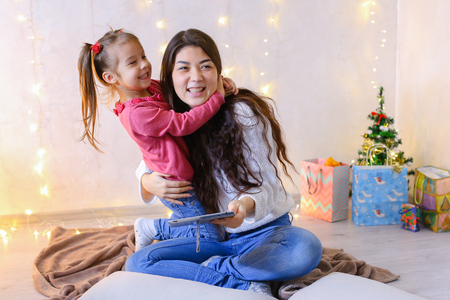 Beautiful girl and elder sister of small female child cares for younger sister and talks, fools around and laughs cute in family way, sitting on floor in bright room against backdrop of glowing garland and small festive tree on eve of new year. Woman with long dark hair of European appearance dressed in white sweater with long sleeves and blue jeans, small female brunette with two tails on each side dressed in raspberry Sweater and blue jeans. Concept of happy and carefree childhood, family values and holidays together, bright and unforgettable New Years childrens emotions, Christmas gifts and Santa Claus, childrens entertainment and fun games, decor and bright festive interior. Stock Photo