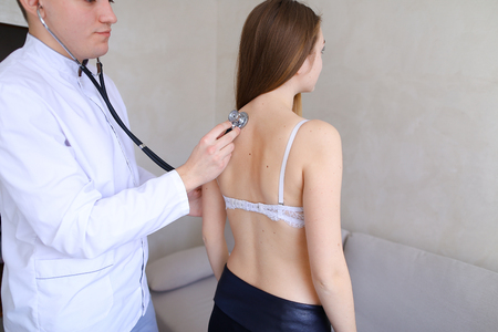 Professional male doctor advises and conducts general examination, applies stethoscope to back and listens to deviations of cute girl who came to reception and complains about health. Imagens