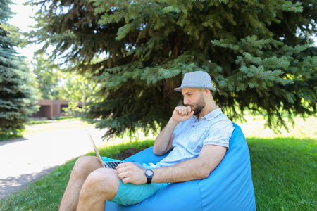 Gladden man sitting in bag chair and looking at camera with close up face near spruce. Handsome guy wears grey hat and t shirt. Concept of  good looking male model resting with gadget outside. Stock Photo