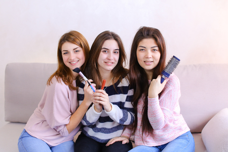 Charming young women look at camera lens and pose, smile and laugh, hold cosmetics and combs, beauty objects and sit on soft gray sofa in bright room in evening.