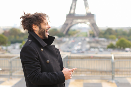 Brazilian boy chatting with European friends near Eifel Tower on smartphone. Young man dressed in black coat, has earing, black curly hair and beard. Concept of Internet innovations apps for communication and positive emotions.