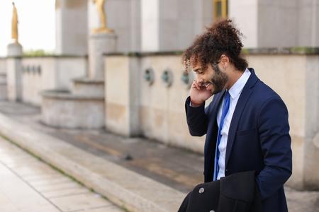 楽しみを持って幸せな若い男の子は、バックグラウンドでエッフェル塔の近くにスマートフォンで友人と話しています。フランス旅行や有名な場所