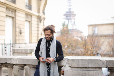 Mulatto tourist raving with white in ear headphones and smartphone near Eiffel tower. Jocund guy visiting Paris and enjoying with popular songs. Concept of using modern gadgets for entertainment and trip to France. Banque d'images